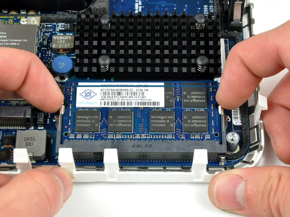 "Image 1/2: Simultaneously pull the tabs on each side of the RAM chip away from the center of the chip. These tabs lock the chip in place and releasing them will cause the chip to ""pop"" up."