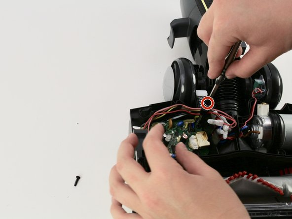 Remove one 15mm T10 screw from the inside left of the base of the vacuum to access the motherboard.