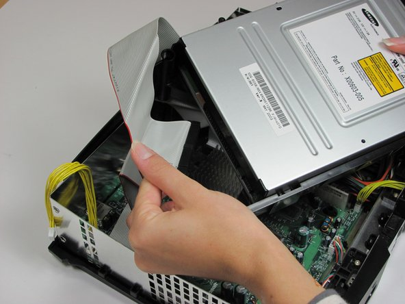 Unplug the ribbon cable and yellow cables from back of disk drive.
