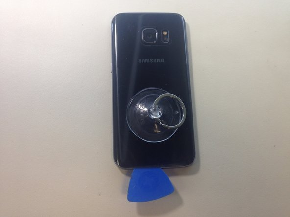 Once you have enough of the back plate lifted to fit a guitar pick, insert one underneath. Slide the guitar pick around the entire edge of the phone to break the adhesive.