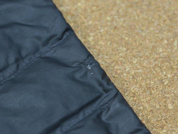Individuare lo strappo nella giacca in piume. Per evitare che le piume fuoriescano dallo strappo sarà necessario sostituire l'intero riquadro trapuntato.