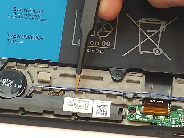 Use tweezers to help lift the white and blue wires connecting both speakers.