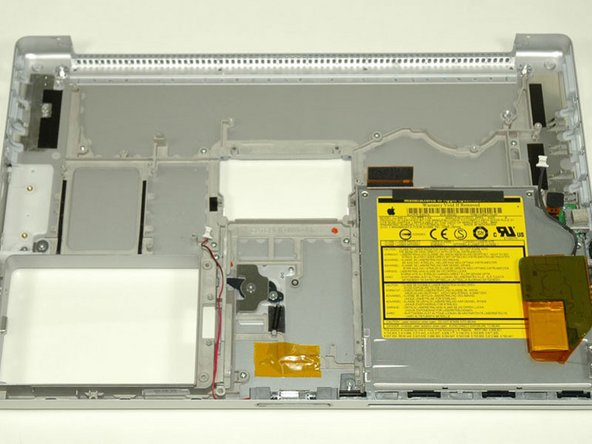 Remove the single black Phillips screw from the front right corner of the optical drive.