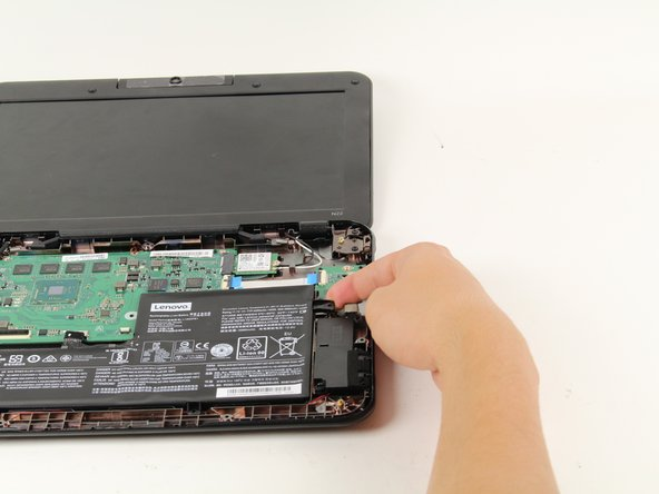 Lift up on the tabs that were held down by the screws to remove the battery.