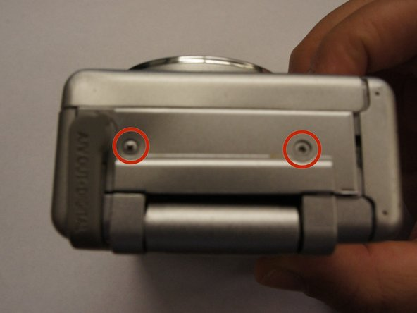 Locate and remove two screws on the same side of the camera as the marked A/V port (2x small Phillips head).
