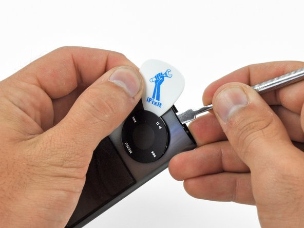 Place a guitar pick between the click wheel and the case of the Nano and remove the metal spudger.