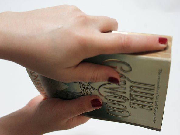 Image 1/1: Firmly drag your fingers down the spine of the book to avoid any air pockets.