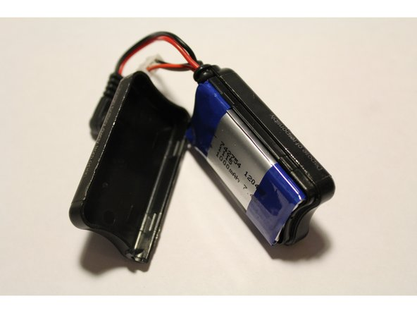 Image 3/3: Separate the two plastic case shells to expose the battery inside.