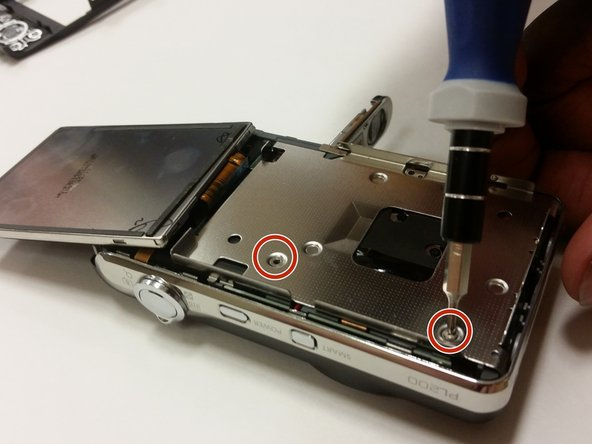 Flip the LCD screen forward and remove the two 3mm screws beneath it using the #000 Phillips Screwdriver.