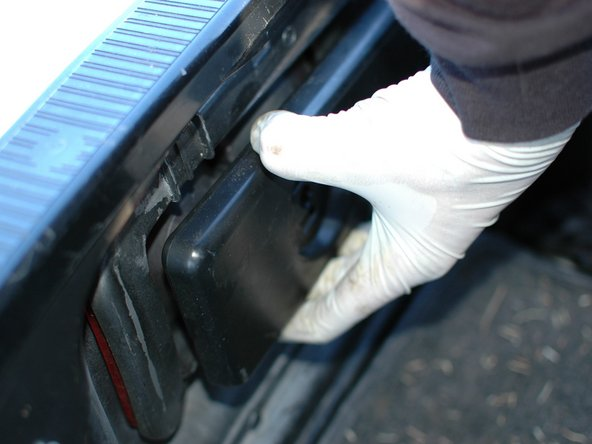 Pull the panel out and away from the back of the car, being careful not to force the bulbs out of the holes.