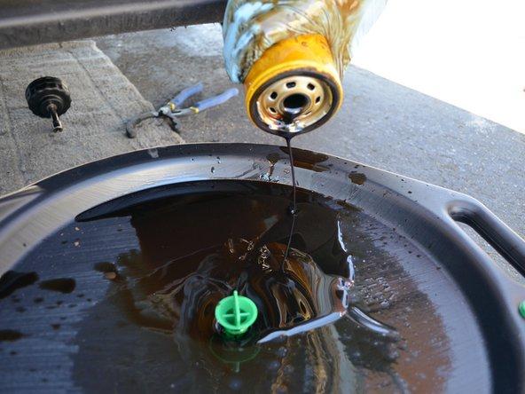 Une fois que le débit d'huile est presque arrêté, continuez à enlever le filtre à la main. Il reste toujours de l'huile dans le filtre, donc laissez-la s'écouler complètement dans le bac pendant vous continuez la vidange.