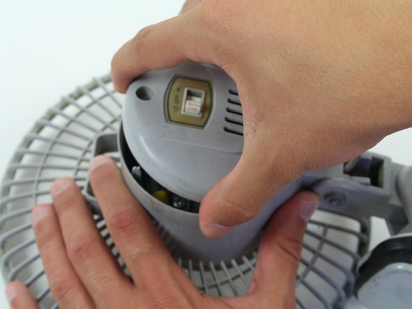 Image 2/3: Start with the fan on its back. Unscrew the back panel to expose the internal wiring.