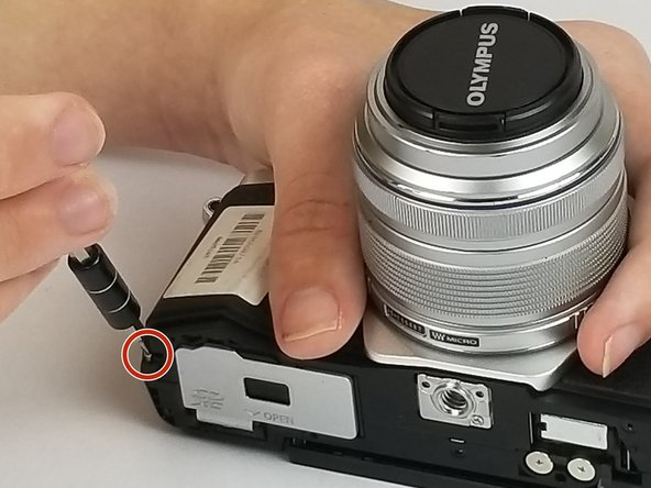 Continuing to use the size PH00 Phillips-head screwdriver, remove the two 3/5 inch screws revealed after removing the bottom plate of the camera.
