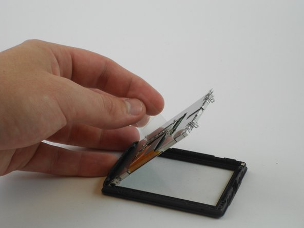 Finally, remove the LCD screen by grabbing the clear plastic tab and lifting it carefully.