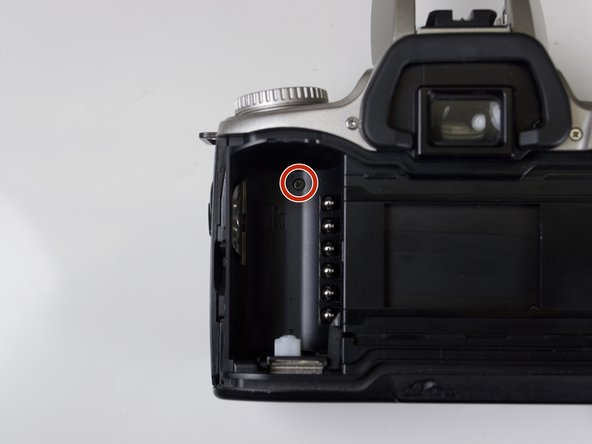 Remove the black Phillips #00 5.0 mm screw from the back of the film compartment.