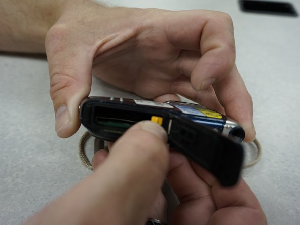 Pull orange tab to the side to release the battery.