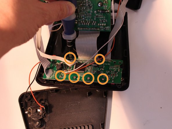 Image 1/3: Press black holding clips down and outward to release display circuit board.