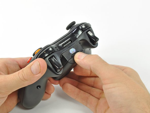 Image 1/2: Remove the battery holder from the controller.