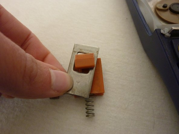 After that, push the metal chip in the notch and press the spring behind the small metal chip.