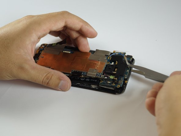 Reach beneath the motherboard with the tweezers, grip it and lift.