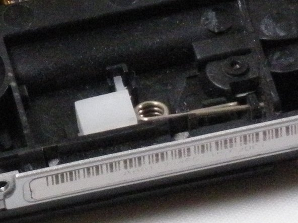 Remove the white plastic box and spring from the PSP.