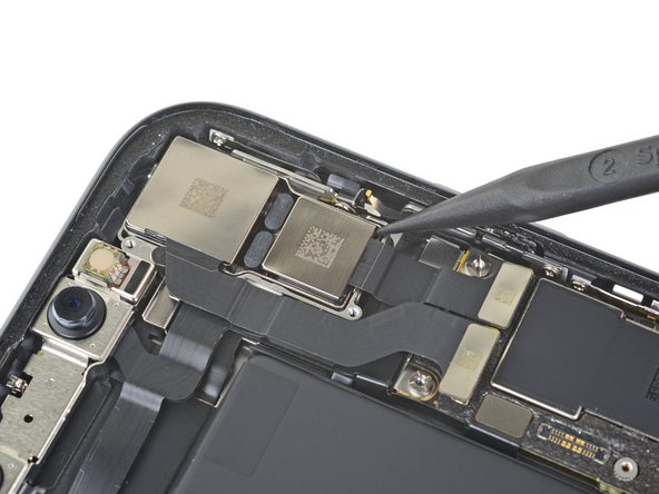Insert the point of a spudger at the bottom right corner of the camera, between the camera assembly and the iPhone's frame.