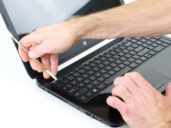 Using either a credit card or flat spudger, wedge it between the palm rest and the keyboard.
