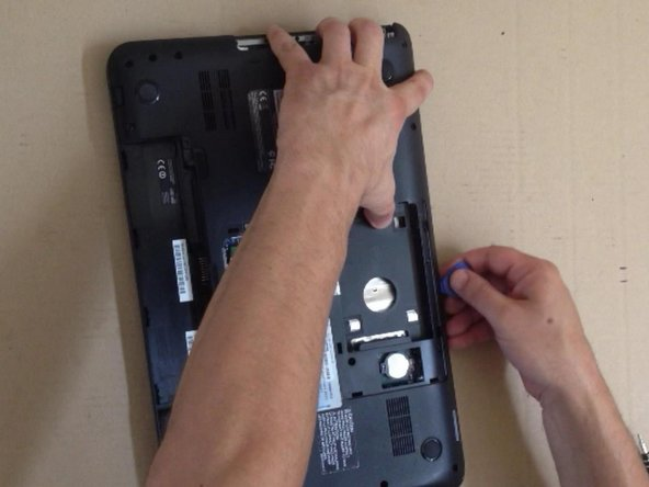 Use a plastic tool for separating the bottom case from the laptop.