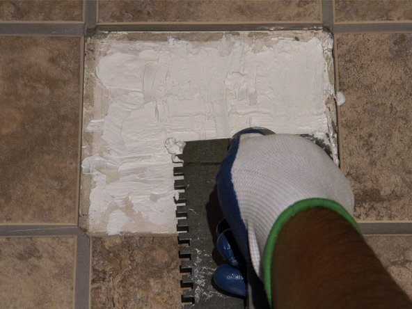 Apply new adhesive using the trowel, making sure the adhesive is spread evenly.