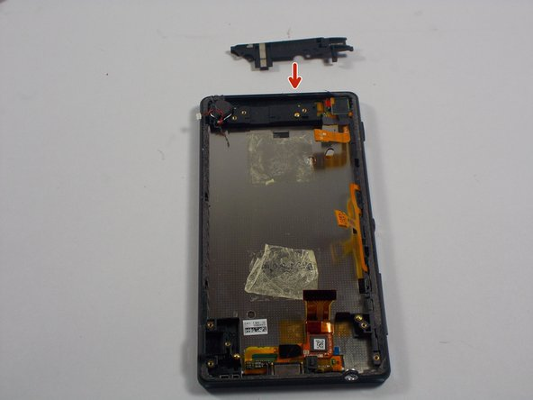 With the battery gone. We next pry off a plastic covering that is located at the top of the phone with the metal spatula.