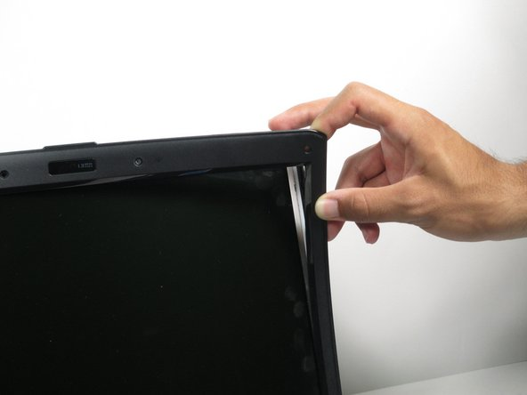 Gently pry the bezel towards you to remove it from the back panel of the laptop.