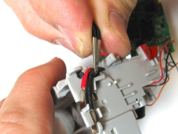 Use the tweezers to remove the tape and rubber strap to begin unraveling the wires from the plastic hooks.