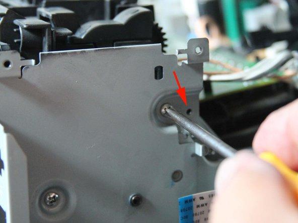 Lüfter ist mit einer Schraube (roter Pfeil) an diesem Blech gesichert: Schraube lösen und  auf der anderen Seite des Lüfters die Arrettierung lösen.