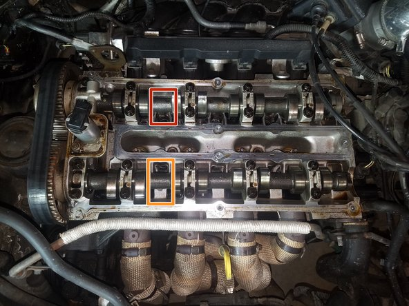 There is a T55 Bolt holding the exhaust sprocket in place.  While holding the camshaft with a proper open end wrench, loosen but do not remove this bolt.  This will allow the camshaft sprocket to rotate.
