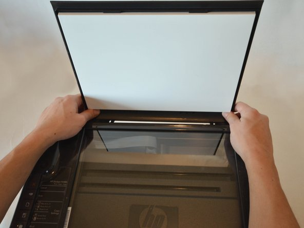 Open the protective lid that is covering the glass. Press gently against the base of the panel to remove the lid from the rest of the printer.