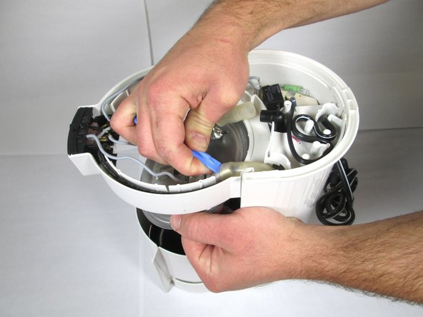 Using the larger plastic opening tool, gently push the tubing off of the valve located on the side. (If the tubing is being stubborn and won't come off, run the Spudger tool around the inside of tubing to free it up.)