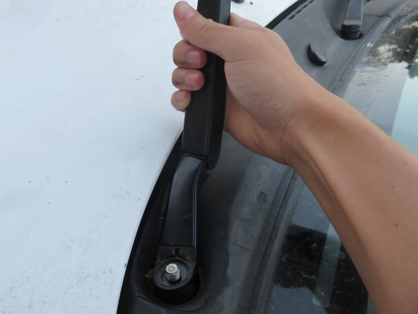 Take your wiper arm, and center its hole on the exposed metal threading.
