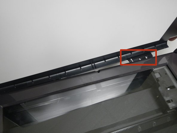 The scanner flap is attached by a clip that can be dislodged by pulling it gently away from the printer.