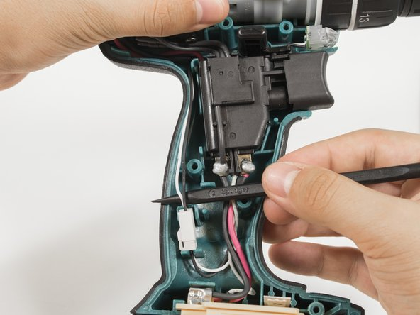 Use the pointed edge of a spudger to pull out the black and white wires located on the left hand side of the drill.