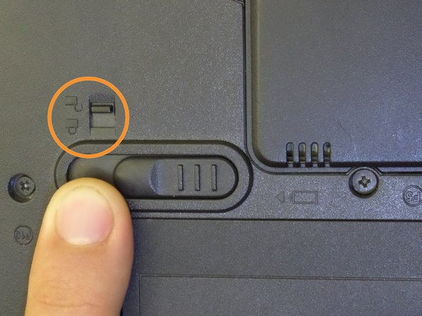 Image 2/2: Use any finger to move the smaller switch above the battery to the unlock position.