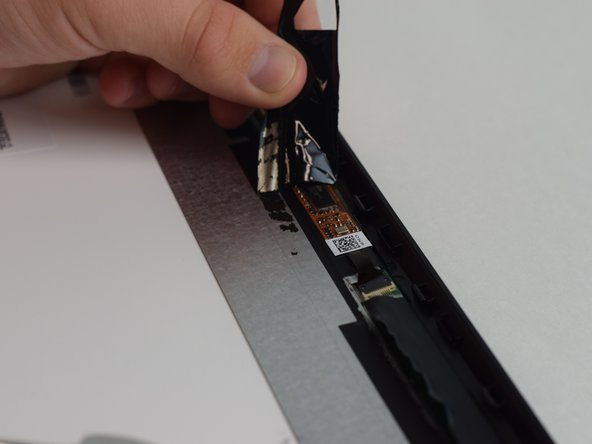 Once adhesive tape is removed, use the pry tool to remove the tab in the corner.  Repeat in each corner.