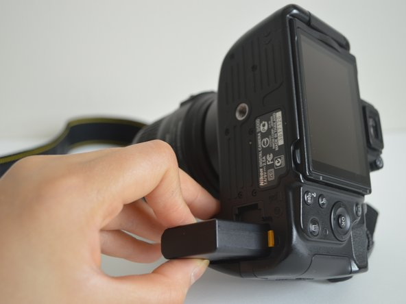 Insert the battery into the battery compartment at the bottom of the camera.