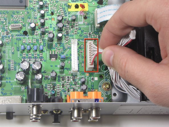 Remove the second of two ribbon cables connected to the Left-Side Motherboard (Green) by pulling vertically.