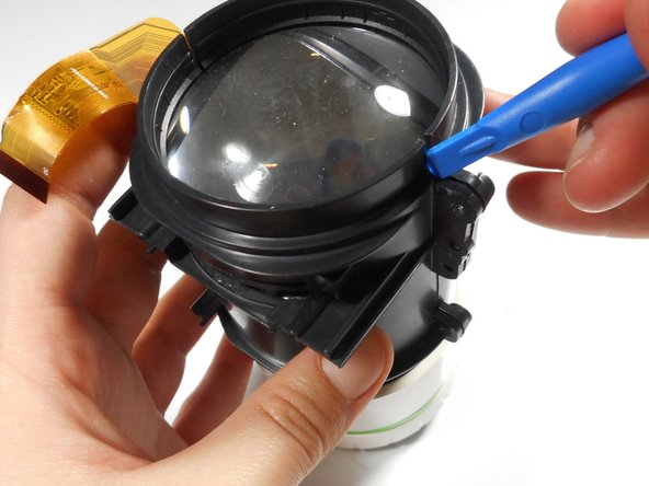 Using the plastic opening tool, slightly separate the casing holding the large lens in place.