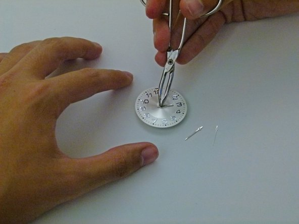 Using your tweezers again, place the minute hand in the center of the face.