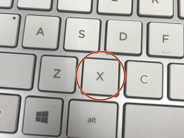 Gently press the key down. It should snap back into place