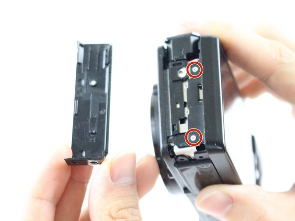 Image 1/1: Remove the two marked screws with a Phillips #000 screwdriver.