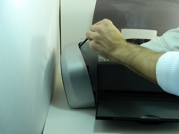 Image 1/1: Open the printer's cover, place your hand inside the right panel and unclip it from the rest of the printer with your thumb and forefinger.