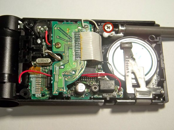 Image 1/2: Using a Philips head #2 screwdriver, remove the screw holding the antenna in place.