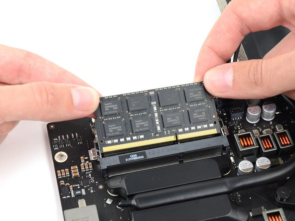 Grab the top left and right corners of the RAM module and carefully pull it straight out of its socket.